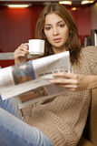 vuxet kaffe som dricker den mitt- nyheternaavläsningskvinnan Royaltyfri Bild
