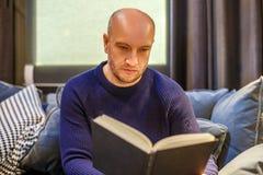 Vuxet mansammanträde på soffan och läsningen en bok arkivfoto