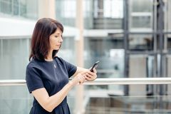 Vuxna affärskvinnor i dräkt genom att använda smartphonen arkivbild