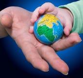 vuxna barn ger jordklotet till Royaltyfri Bild