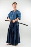 Vuxna caucasian manliga utbildande Iaido omkring som drar ett japanskt svärd med fokuserad blick arkivfoto