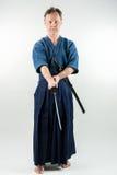Vuxna caucasian manliga utbildande Iaido som rymmer ett japanskt svärd med fokuserad blick arkivbilder
