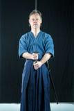 Vuxna caucasian manliga utbildande Iaido som rymmer ett japanskt svärd med fokuserad blick royaltyfri fotografi