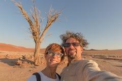 Vuxna caucasian par som tar selfie på Sossusvlei i den Namib öknen, Namib Naukluft nationalpark, huvudsaklig loppdestination i N royaltyfri bild