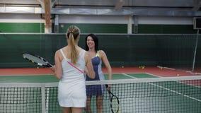 Vuxna kvinnor avslutade tennismatchen, en kvinna i den vita sportswearen segrade konkurrensen, idrottskvinnakramen och skakan lager videofilmer