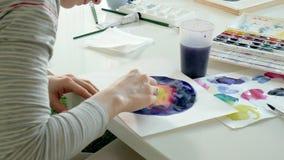 Vuxna kvinnor målar med kulöra vattenfärgmålarfärger i en hem- studio