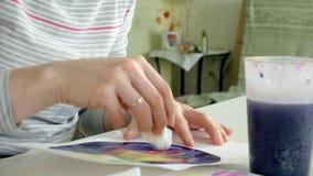 Vuxna kvinnor målar med kulöra vattenfärgmålarfärger i ett hem- studioslut upp lager videofilmer