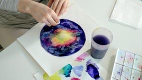 Vuxna kvinnor målar med kulöra vattenfärgmålarfärger i ett hem- studioslut upp