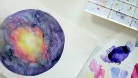 Vuxna kvinnor målar med kulöra vattenfärgmålarfärger i ett hem- studioslut upp stock video