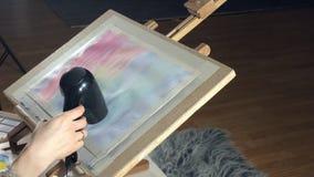 Vuxna kvinnor målar med kulöra vattenfärgmålarfärger och torkar med en hårtork i en konstskola arkivfilmer