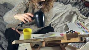 Vuxna kvinnor målar med kulöra vattenfärgmålarfärger och torkar med en hårtork i en konstskola stock video