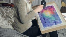 Vuxna kvinnor målar med kulöra vattenfärgmålarfärger och torkar med en hårtork i en konstskola