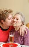 Vuxna kvinnor som kramar hennes höga moder Royaltyfri Foto