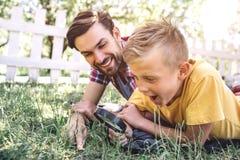Vuxna människan och barnet ligger på gräs utanför i parkerar Pojken ser ner till och med ögla Han förbluffas Hans farsa är dessut royaltyfri bild