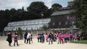 Vuxna människor och barn i botaniska trädgården nära växthuset i Paris arkivfilmer