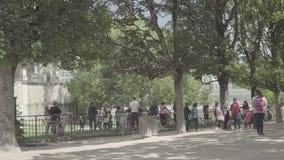 Vuxna människor och barn i botaniska trädgården nära växthuset i Paris stock video