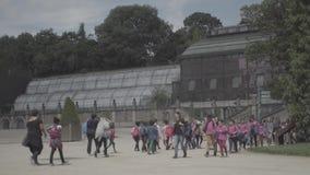 Vuxna människor och barn i botaniska trädgården nära växthuset i Paris lager videofilmer