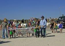 Vuxna människor och barn leder den barfota Mardi Gras Parade Arkivfoton