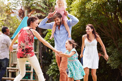 Vuxna människor och ungar som har gyckel som spelar i en trädgård arkivfoton
