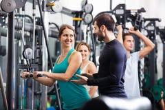 Vuxna människor som gör powerlifting på maskiner Royaltyfri Fotografi