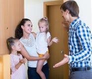 Vuxna människor och ungar som möter på dörröppningen och hälsar sig Royaltyfria Bilder