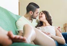 Vuxna par på soffan i hem Royaltyfri Bild