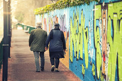 Vuxna par som går handen - in - hand nära en väggmålning med grafitti Royaltyfri Foto