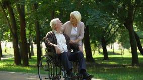 Vuxna par som in går, parkerar, frun som kysser hennes rörelsehindrade make, rehabilitering stock video