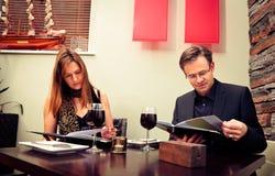 Vuxna par som läser menyn Royaltyfri Bild