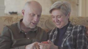 Vuxna par som sitter på den stora soffan och den skalliga kvinnan som visar foto i mobiltelefonen för hans gamal man med korta gr lager videofilmer