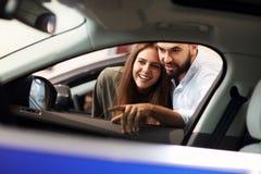 Vuxna par som väljer den nya bilen i visningslokal arkivfoto