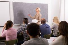 Vuxna studenter med läraren i klassrum Arkivbild