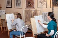 Vuxna studenter sitter på staffli, lär att dra royaltyfri fotografi