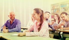 Vuxna studenter som skriver i klassrum arkivbild