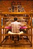 Vävare som använder handvävstolen som gör sarien Arkivfoto