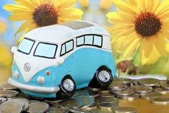 VW-bus als spaarvarken op euro muntstukken Stock Foto's