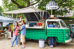 VW food truck. DORDRECHT, NETHERLANDS - July 26, 2015: Serving drinks out of an old timer bus decorated with retro artifacts, a couple waits while the drink is Royalty Free Stock Images