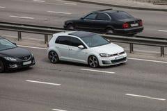 VW Golf white speeding on empty highway stock photos