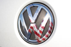 VW / Volkswagen Logo, US American flag. Wolfsburg, Germany, November 19, 2015: Volkswagen Logo, VW is cheating in tests for pollution and emissions of its diesel Royalty Free Stock Images