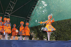 Vyaznikovskiy theatre of the baby mode on scene at day of the ci. Children in beautiful orange suit show baby mode on scene at day of the city Mstyora Royalty Free Stock Photo