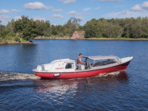 Vyborg, Russia - September 08, 2016: Man controls the motor boat floats on the lake Stock Photos