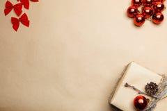 Vykort för nytt år med gåvan på ecostil och röda pilbågar och bubblor Royaltyfri Fotografi