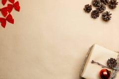 Vykort för nytt år med gåvan på ecostil och röda pilbågar och pinecones Fotografering för Bildbyråer