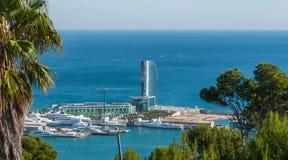 Vykort från Spanien Portar i Barcelona - solglints av exponeringsglaset på en segla formad byggnad på en man gjorde av ön royaltyfri bild