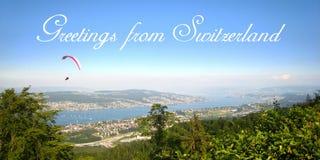 Vykort med en härlig sikt i soligt sommarväder över yachter, segelbåtar och paraglidingsportar på sjön Zurich royaltyfri bild