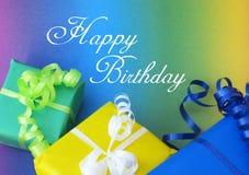 Vykort med färgglade gåvor i gul skrifttext för grön och blå och lycklig födelsedag royaltyfri foto
