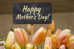Vykort med kräm- tulpan och för moder` s för tecken lycklig dag på plattan färgrika blommor för bukett Arkivbild