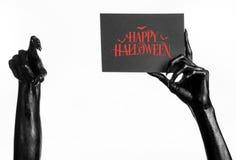 Vykort och lyckligt allhelgonaaftontema: den svarta handen av död som rymmer ett pappers- kort med den lyckliga allhelgonaaftonen Arkivfoton