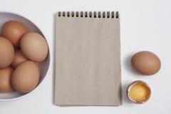 Vykorten för recept Ägg i en vit platta, ett helt ägg bredvid det brutna ägget på tabellen på den vita bakgrunden Royaltyfria Foton