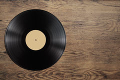Vynil record disc on wooden table Royalty Free Stock Photo